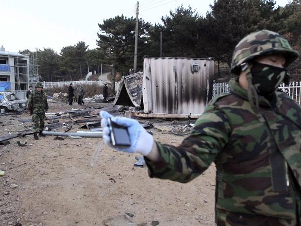 Militar sul-coreano barra fotógrafo que tentava entrar  nesta quarta-feira (24) em área de escombros na ilha atacada.