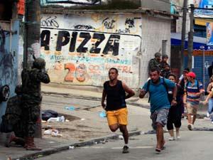 Moradores do Alemão correm durante operação policial