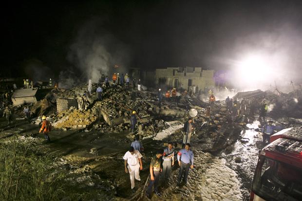 Bombeiros apagam o fogo após queda do avião em Karachi.
