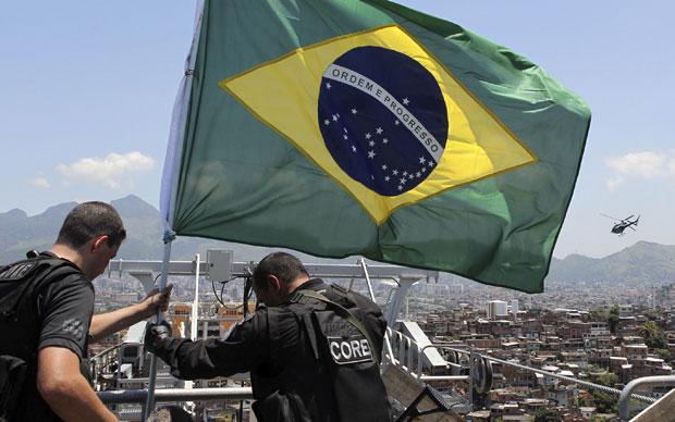 Bandeira do Brasil no topo do morro marcou consquista das forças de segurança no Morro do Alemão, no Rio, neste domingo (28)