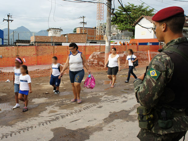 Crianças do Conjunto do Alemão seguem para a escola sob vigilância de militares