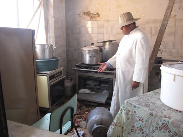 O padre Barnabé mostra a cozinha da igreja toda revirada
