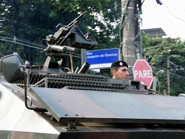 Carro militar está parado em rua que recebeu placa de identificação nesta quinta-feira