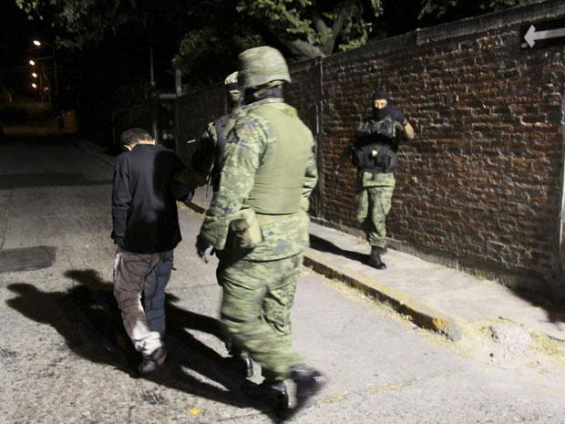Soldados escoltam Edgar Jimenez Lugo, conhecido como 'El Ponchis', após apresentação à mídia