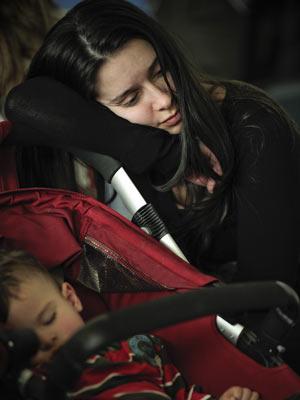 Passageira colombiana descansa ao lado de carrinho com bebê no aeroporto de Bilbao, no norte do país