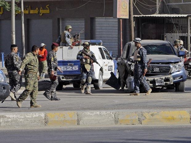 Efetivos de segurança iraquianos inspecionam o local de um dos ataques explosivos, neste sábado (4)