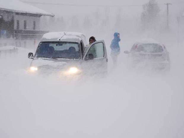 Neve obriga motoristas a pararem em rua próximo a St. Ulrich, na província austríaca do Tirol, nesta sexta-feira (10).