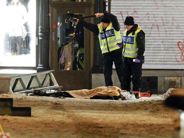 Policiais examinam o corpo de um homem no centro da cidade de Estocolmo.