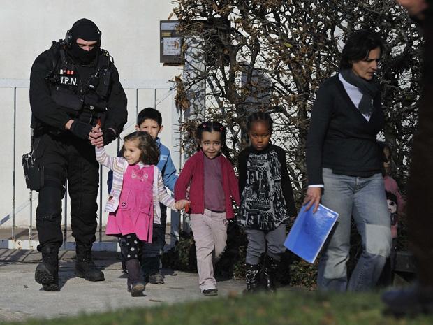Policiais de forças especiais retiram as crianças da escola após o fim do sequestro nesta segunda-feira (13) em Besançon.