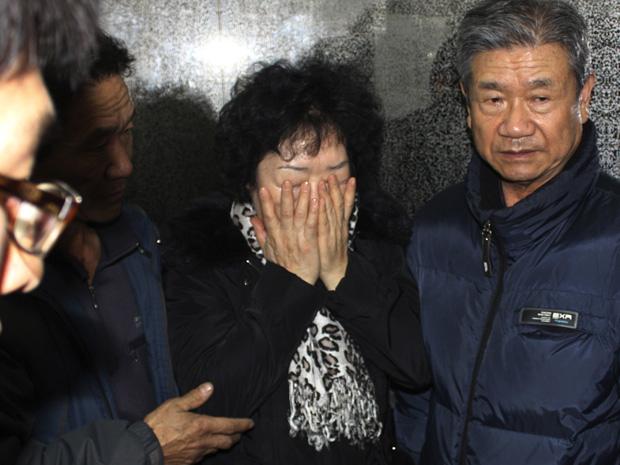 Parente de marinheiro chora em Busan, na Coreia do Sul, nesta segunda-feira (13).