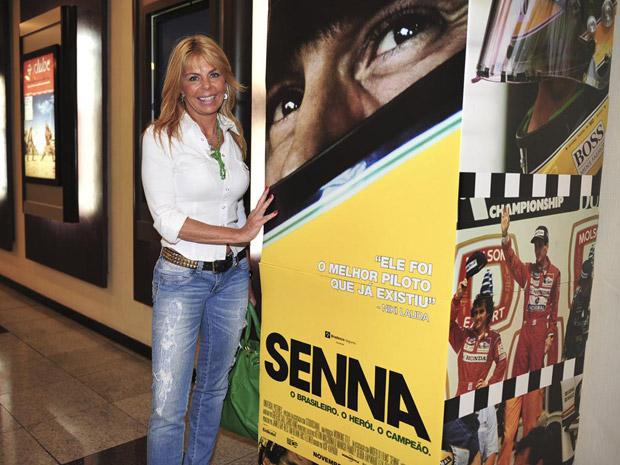 Lilian ao lado de banner do filme Senna
