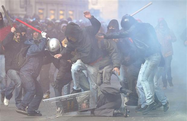 Policial é cercado e agredido por manifestantes nesta terça-feira (14) no centro de Roma.