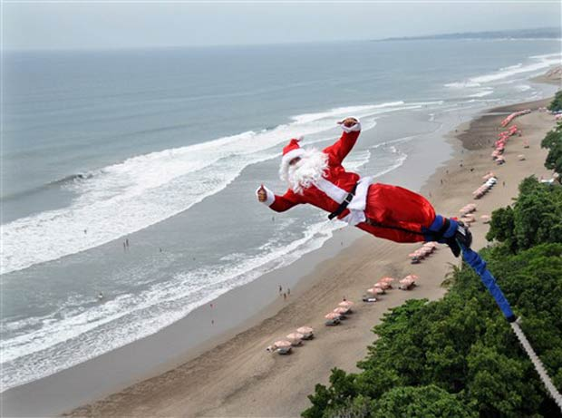 Vestido de Papai Noel, homem salta de bungee jump, na quinta-feira, em praia em  Kuta, na Indonésia.