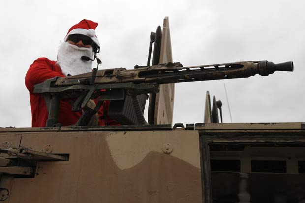 Soldado do exército alemão é flagrado vestido de Papai Noel em cima de um veículo blindado em Kunduz, no Afeganistão, no dia 6 de dezembro.