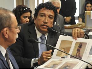 O presidente da Comissão Parlamentar de Inquérito (CPI) da Pedofilia no Senado, Magno Malta, mostra álbuns de fotos apreendidos em diligências no Amazonas