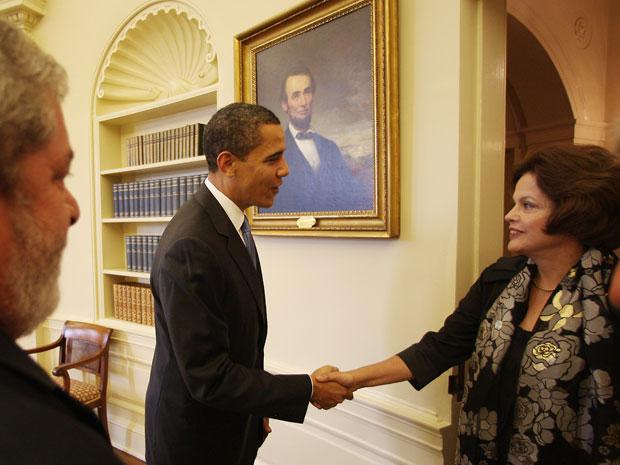 Presidente Lula observa a então ministra Dilma Rousseff ser recebida pelo presidente Barack Obama, em Washington, em março de 2009
