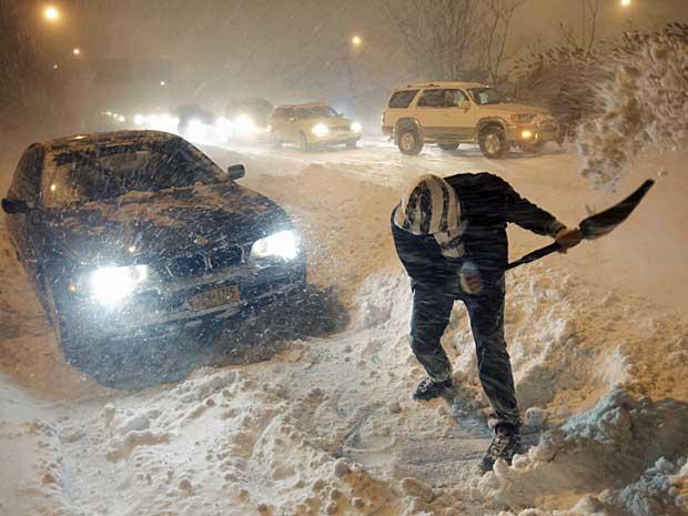 Homem retira neve com uma pá para mover seu carro, em Long Island, Nova York.