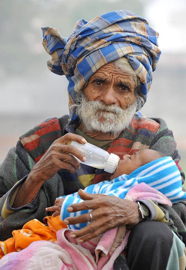 """O indiano Ramjit Raghav, de 94 anos, dá mamaneira para seu filho Vikramjeet, de dois meses, em 28 de dezembro, em Kharkhoda. Ele reivindica o título de """"novo pai"""" mais velho do mundo. Raghat trabalha como """"diarista"""" em uma fazenda e afirmou que quer ter mais um filho no ano que vem."""