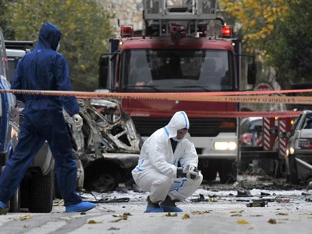 Peritos analisam destroços da bomba que não deixou feridos em frente a tribunal em Atenas, capital da Grécia.