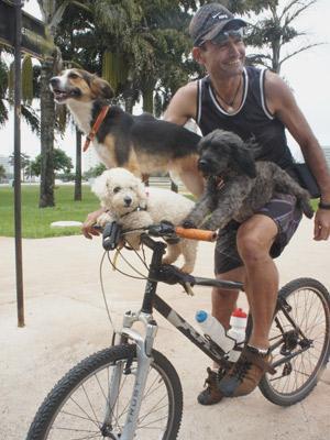 Craig Alden, 41 anos, anda de bicicleta com as tr�s cadelas de estima��o