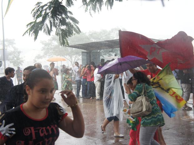 Pessoas tentam se proteger da chuva no começo do desfile de Dilma Rousseff
