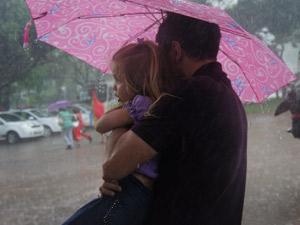 Home tenta se proteger da chuva com a filha no colo