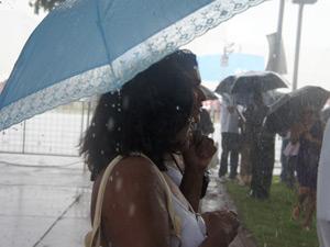Mulher caminha na chuva após passagem de DIlma Rousseff