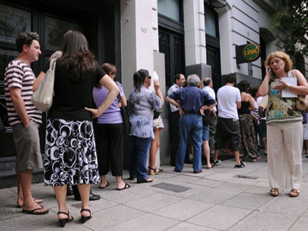 Clientes formam fila em frente à agência assaltada nesta segunda-feira (3) em Buenos Aires.
