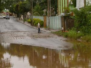 Homem caminha em rua alagada de Hortolândia