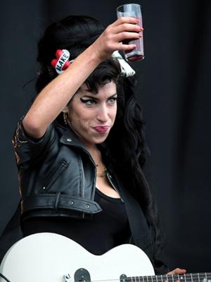 Amy ofecere um drinque ao público durante o festival T in the Park, em julho de 2008, na Escócia (Foto: AFP)