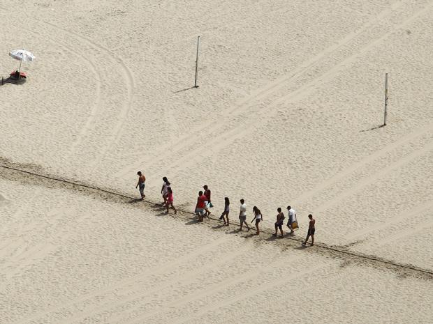 Comerciantes da orla da Praia do Leme e Copacabana, na zona sul do Rio, molharam a areia para criar uma trilha que facilita o acesso dos banhistas à beira da água sem queimar os pés, por conta da areia quente devido ao verão.
