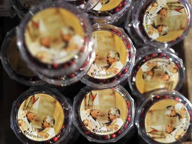 Rosários com as imagens dos papas João Paulo II e Bento XVI são vendidos nesta sexta-feira (14) no Vaticano.