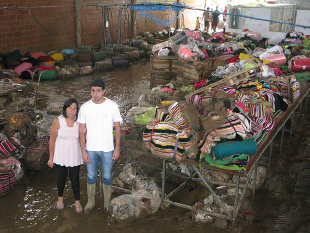 Dona de malharia e filho, com rolos de pano cobertos de lama e instalações destruídas