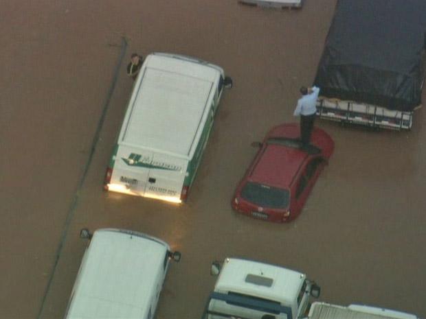 Homem sobe no teto do carro para escapar de alagamento no ABC