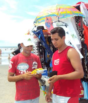 Edil Jorge (D) paga suas compras com cartão de crédito no carrinho de Carlos Roberto.