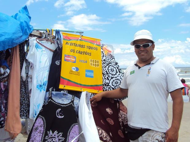 Custódio Anibal vende produtos de praia nas areias de Mongaguá, no litoral de São Paulo. Clientes podem pagar com cartão de débito ou de crédito.