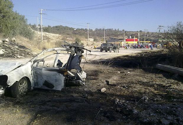 Soldado se aproxima do carro que explodiu em Tula neste sábado (22)