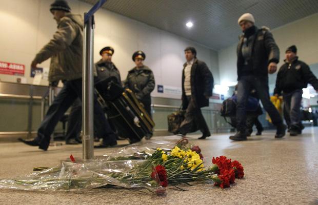 Flores são deixadas nesta terça-feira (25) em homenagem aos mortos pelo atentado da véspera, em saguão no aeroporto russo de Domodedovo; ao fundo, policiais montam guarda.