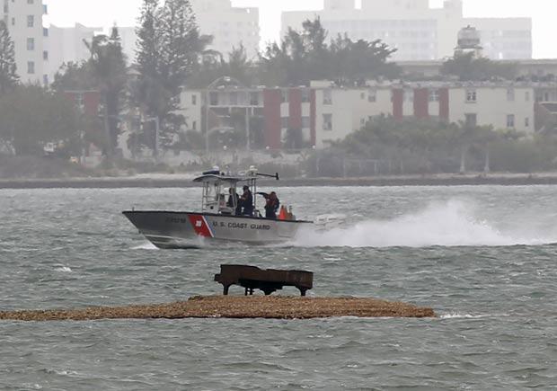 Barco da guarda costeira passa próximo ao local onde está o piano.