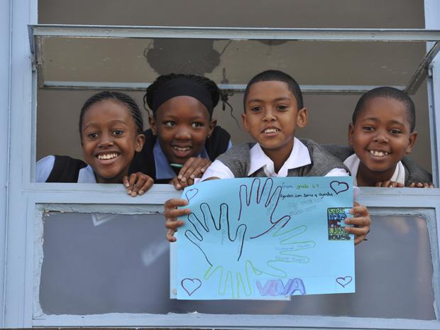 Crianças de escola em frente ao hospital em Johanesburgo mostram cartaz com mensagem para Nelson Mandela nesta quinta-feira (27)