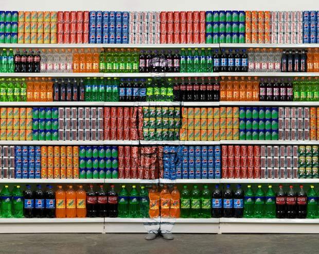 Liu Bolin posa na frente de prateleira de refrigerantes.