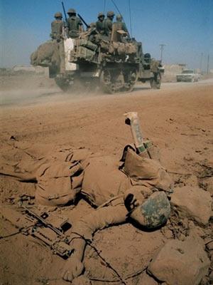 Veículo militar israelense passa por corpo de soldado sírio morto durante a guerra para tentar reaver Colinas do Golã, em 1967