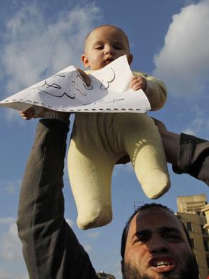 Manifestante ergue bebê durante protesto no Cairo nesta segunda (31)