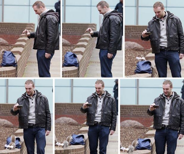 Homem fotografa com seu celular enquanto esquilo 'rouba' lanche de sua mochila nesta segunda-feira (31) no centro de Londres. O 'roubo' foi flagrado pelo fotógrafo Andrew Winning