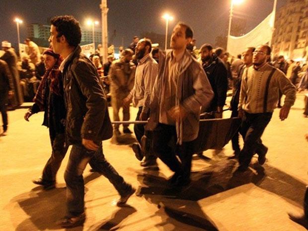 Manifestantes antigoverno carregam um ferido durante confrontos na noite desta quarta-feira (2), na praça Tahrir (Foto: Khaled Desouki / AFP)