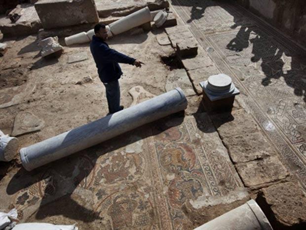 Arqueólogo israelense analisa mosaico no solo da igreja recém-descoberta.