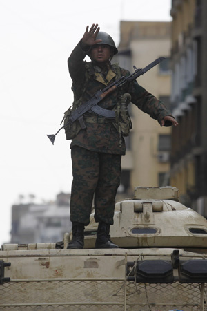 Soldado gesticula sobre tanque na entrada da Praça Tahrir nesta qunta (3) (Foto: AP)