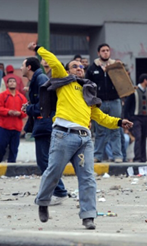 Manifestante antigoverno joga pedra em oponente nesta quinta-feira (3) (Foto: AFP)
