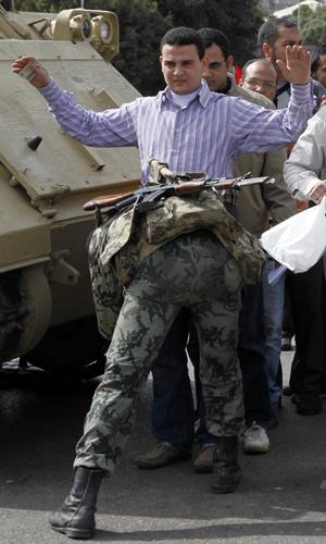 Egípcios são revistados ao chegar à área das manifetações no Cairo (Foto: AP)