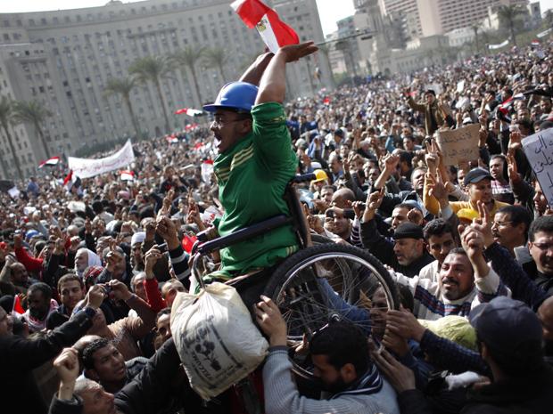 Manifestante em cadeira de rodas é carregado pela multidão na Praça Tahrir nesta sexta (4) (Foto: AP)